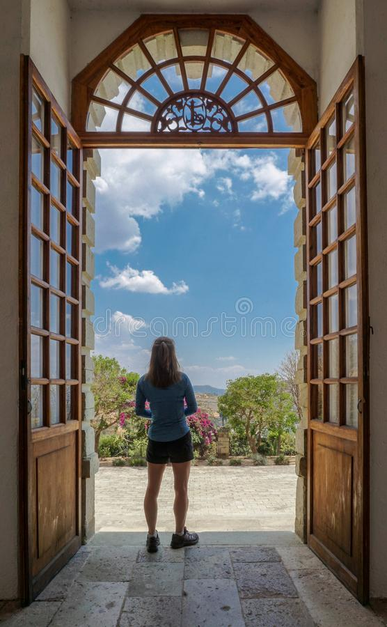 Donna che sta guardante fisso fuori entrata fotografie stock