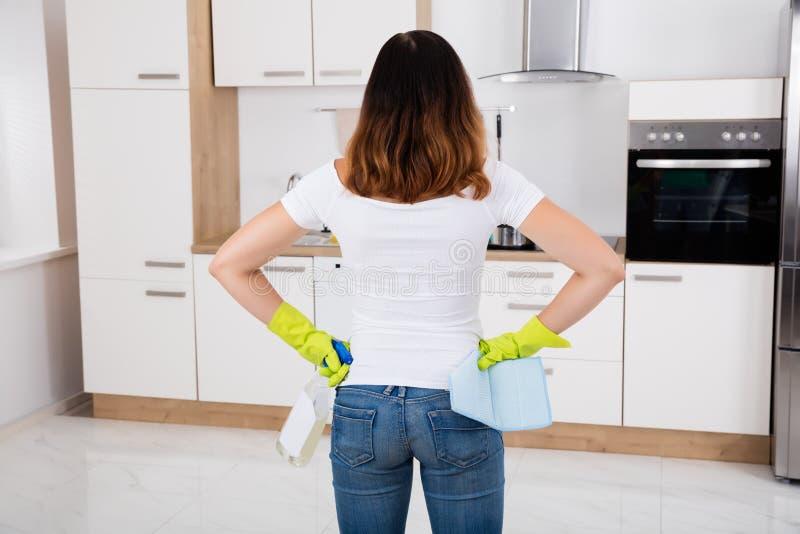 Donna che sta nella cucina facendo uso del prodotto di pulizia fotografia stock libera da diritti