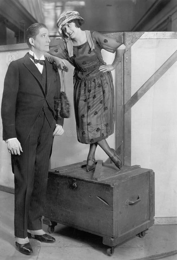 Donna che sta su un tronco accanto ad un uomo molto alto (tutte le persone rappresentate non sono vivente più lungo e nessuna pro immagine stock libera da diritti