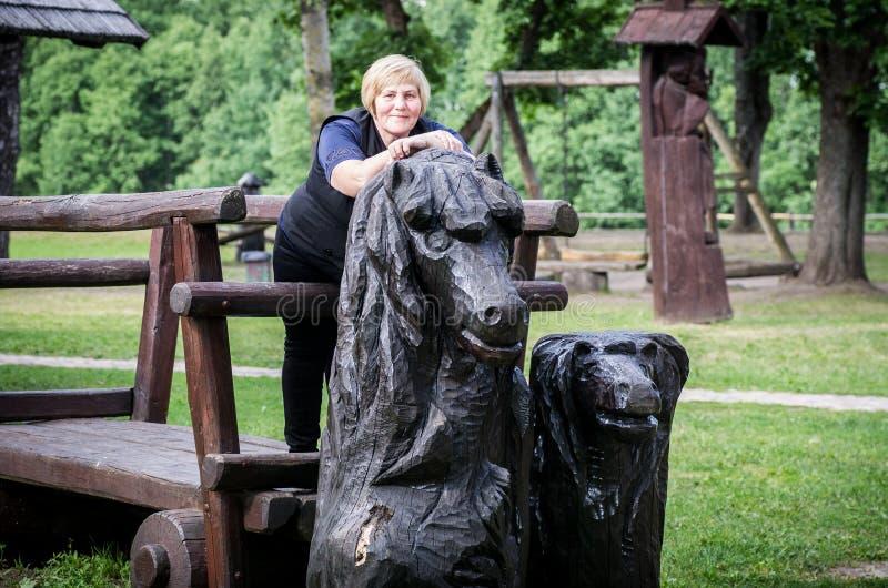 Donna che sta sul carretto di legno fotografia stock