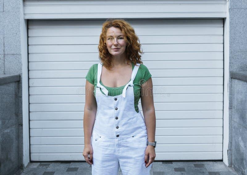 Donna che sta sul modello bianco di minimalismo in camici bianchi Giorno, all'aperto fotografia stock