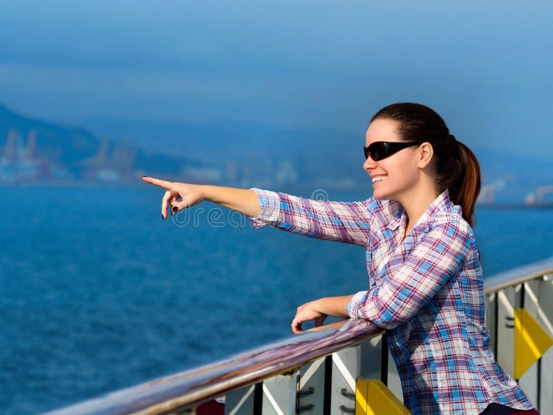 Donna che sta sulla piattaforma di una nave da crociera fotografia stock