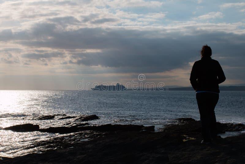 Donna che sta sulle rocce e sulla nave da crociera di sorveglianza immagine stock