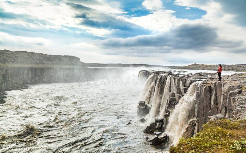 Donna che sta vicino alla cascata famosa di Selfoss nel parco nazionale di Vatnajokull, Islanda di nordest immagine stock libera da diritti