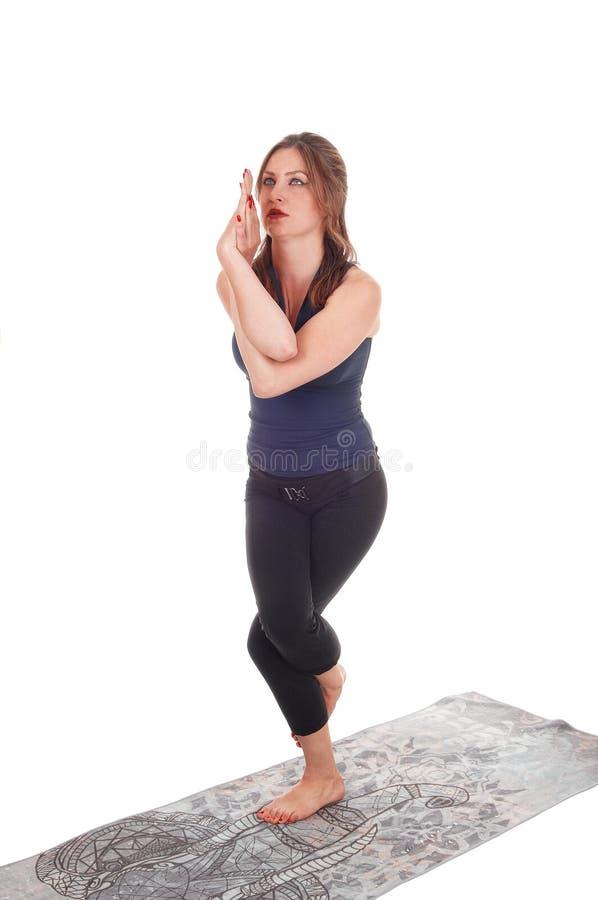 Donna che stanno su una gamba e armi torte fotografie stock