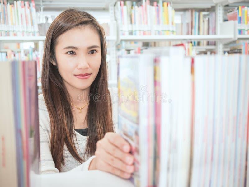 Donna che studia nella biblioteca fotografia stock