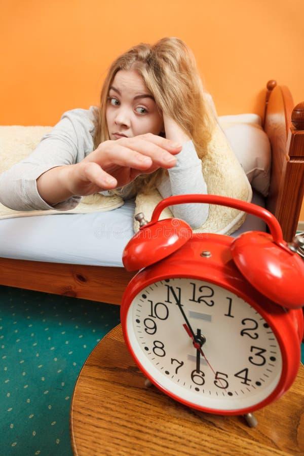 Donna che sveglia spegnebbi sveglia nella mattina fotografie stock