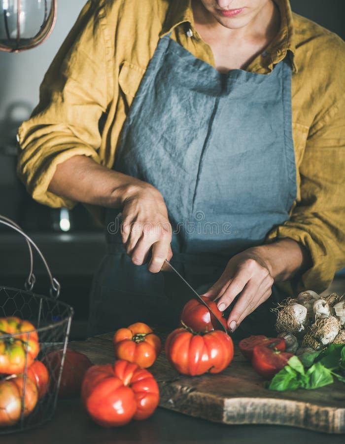 Donna che taglia e che cucina salsa al pomodoro o pasta fotografia stock libera da diritti