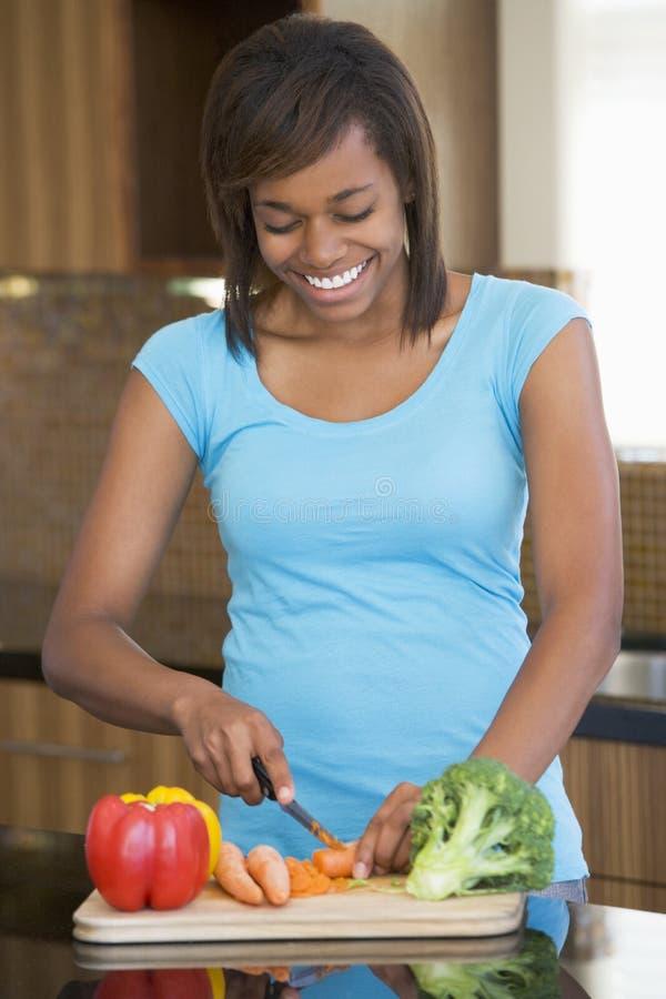 Donna che taglia le verdure a pezzi fotografia stock