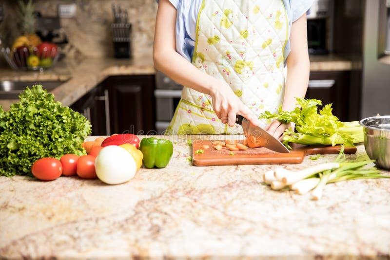 Donna che taglia le verdure a pezzi sul contatore di cucina fotografia stock