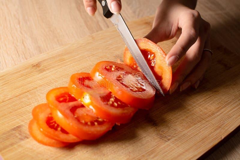 Donna che taglia un pomodoro sul bordo tagliato di legno immagine stock libera da diritti