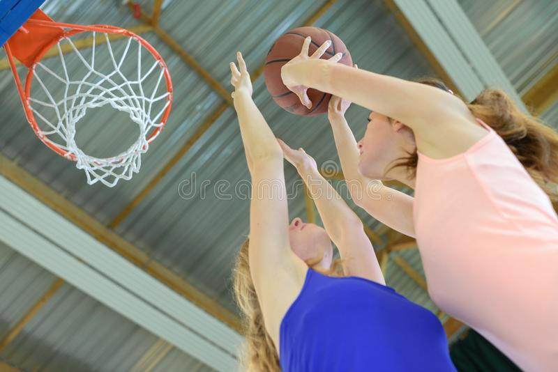 Donna che tende verso la rete di pallacanestro immagine stock