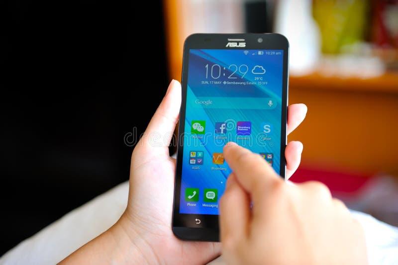Donna che tiene Asus nuovissimo Zenfone 2 fotografia stock libera da diritti