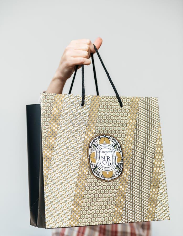 Donna che tiene borsa dorata di lusso da Diptyque Parigi immagini stock libere da diritti