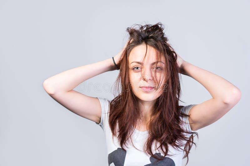Donna che tiene capelli sudici che esaminano macchina fotografica immagine stock libera da diritti