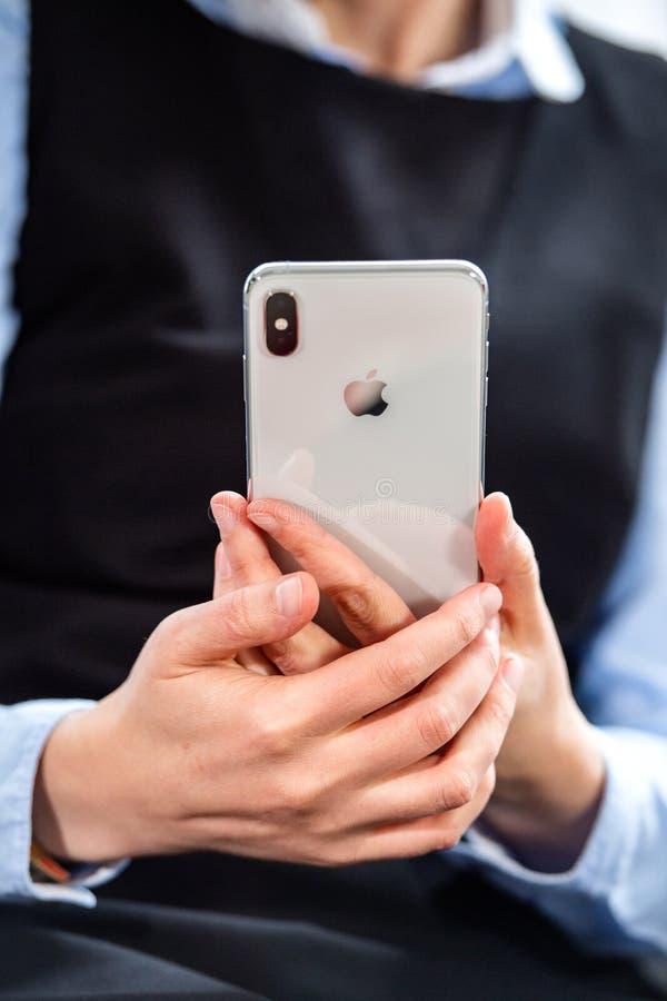 Donna che tiene disponibile massimo di Xs di nuovo iPhone d'argento fotografia stock libera da diritti