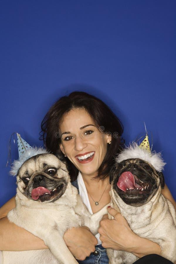Donna che tiene due cani del Pug. fotografia stock libera da diritti