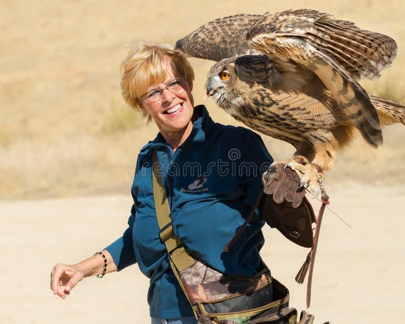 Donna che tiene Eagle Owl euasian sul suo guanto immagine stock