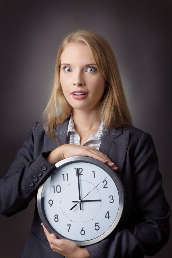 Donna che tiene grande orologio fotografie stock