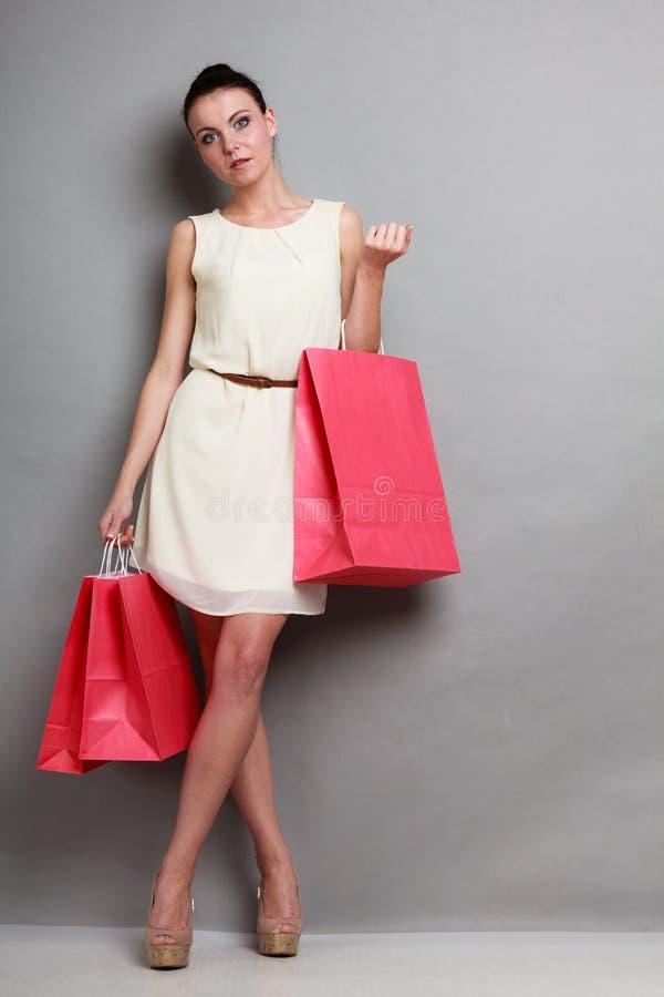 Donna che tiene i sacchetti della spesa di carta rossi fotografia stock