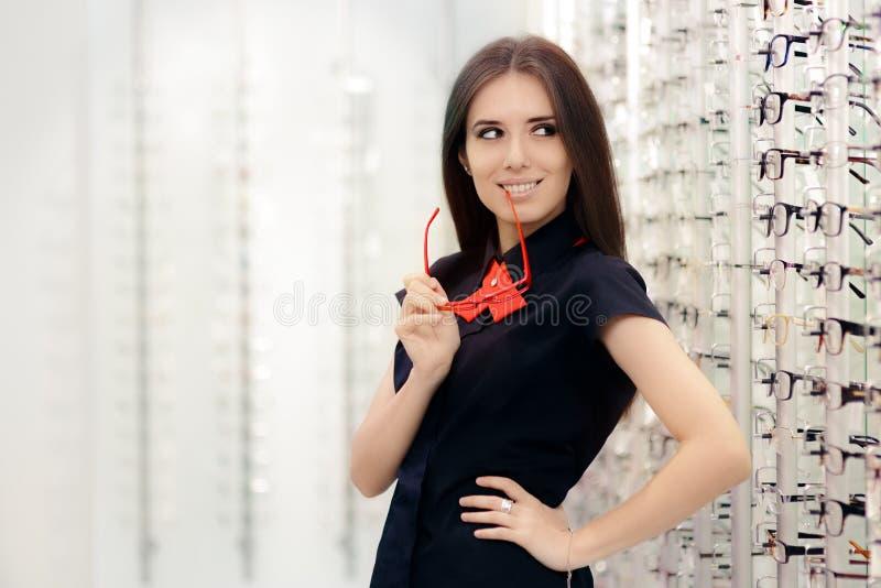 Donna che tiene i suoi vetri in deposito ottico medico immagini stock