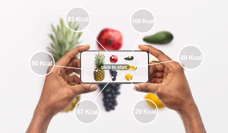 Donna che tiene il cellulare con un'applicazione che conta le calorie immagini stock libere da diritti