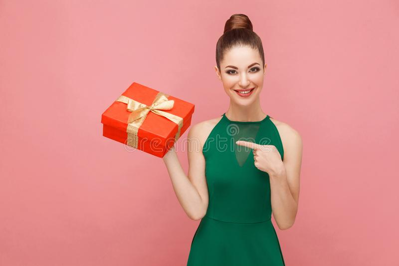 Donna che tiene il contenitore di regalo rosso e che indica dito immagini stock
