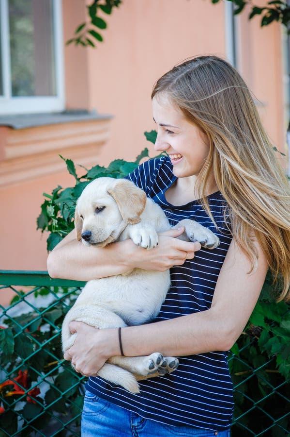 Donna che tiene il cucciolo bianco di labrador fotografie stock