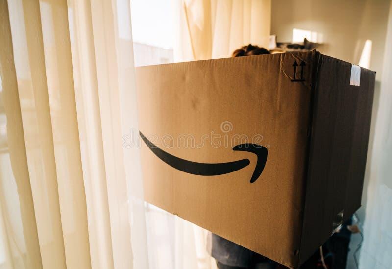 Donna che tiene il grande cartone del pacchetto dell'Amazon Prime fotografia stock libera da diritti