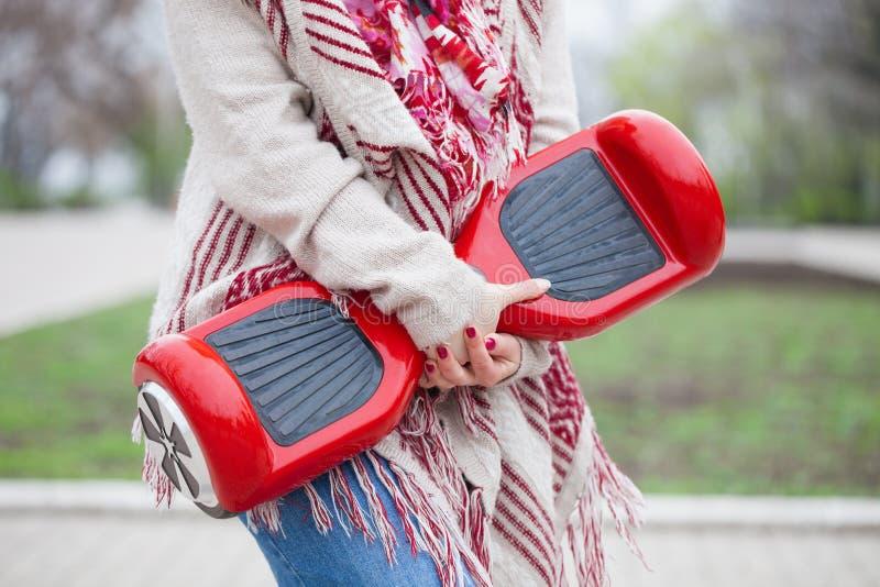 Donna che tiene il mini motorino elettrico rosso moderno di librazione o segway del bordo immagini stock libere da diritti