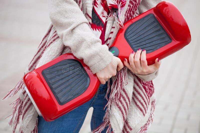 Donna che tiene il mini motorino elettrico rosso moderno di librazione o segway del bordo fotografie stock libere da diritti