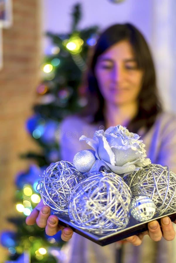 Donna che tiene la palla di natale sopra il fondo delle luci immagine stock libera da diritti