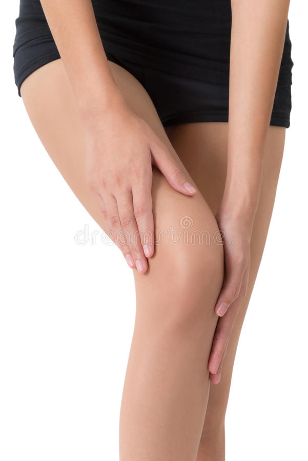 Donna che tiene la sua bella gamba lunga sana con il massaggio del ginocchio nell'area di dolore immagine stock libera da diritti
