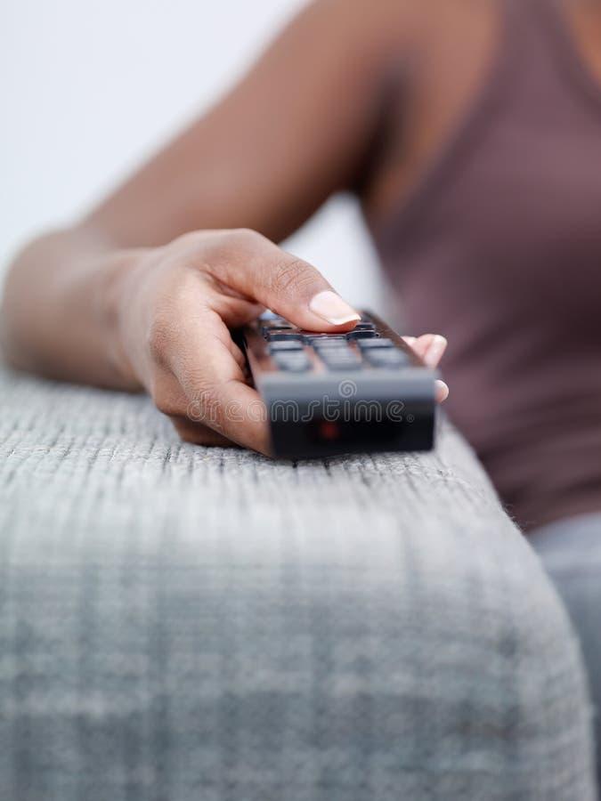 Donna che tiene la TV di sorveglianza e di telecomando immagine stock libera da diritti