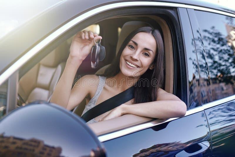 Donna che tiene le chiavi che si siedono nella nuova automobile fotografia stock