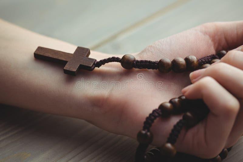 Donna che tiene le perle di legno del rosario fotografia stock