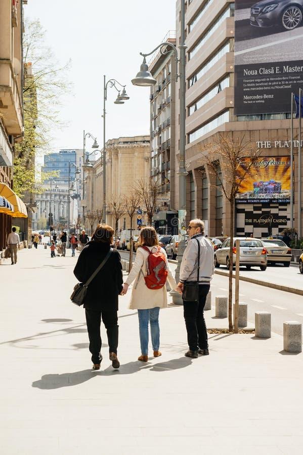 Donna che tiene a mano i suoi genitori che camminano sulla via fotografie stock libere da diritti