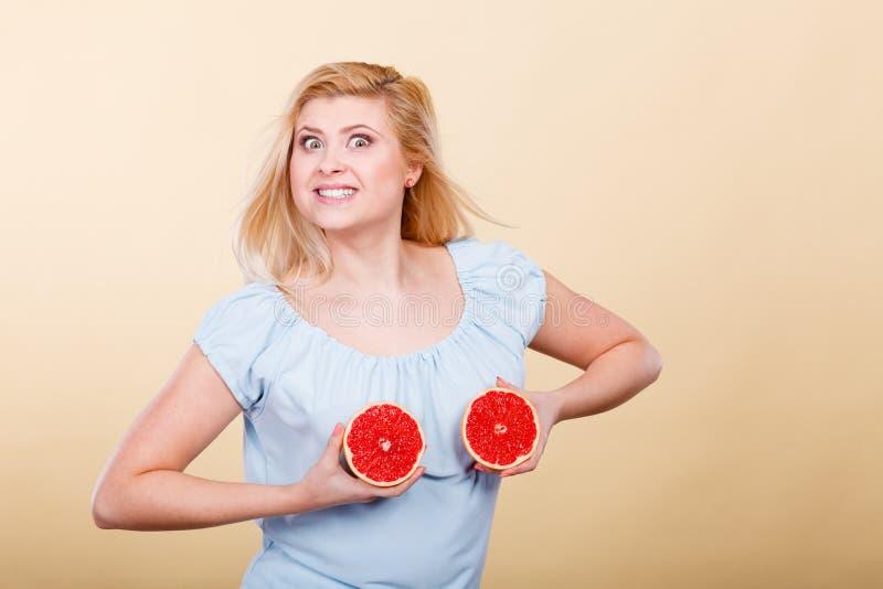 Donna che tiene pompelmo rosso sul seno fotografia stock libera da diritti
