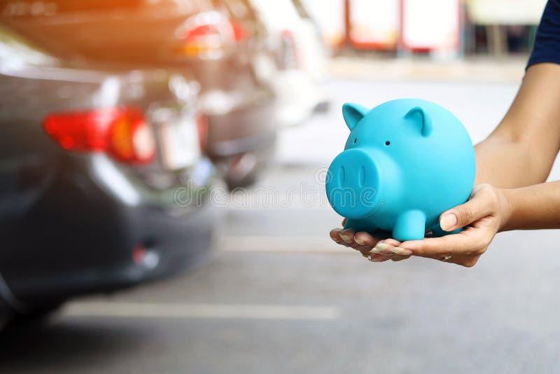 Donna che tiene porcellino salvadanaio blu con la condizione vicino all'automobile per i soldi di risparmi per comprare veicolo & fotografia stock libera da diritti