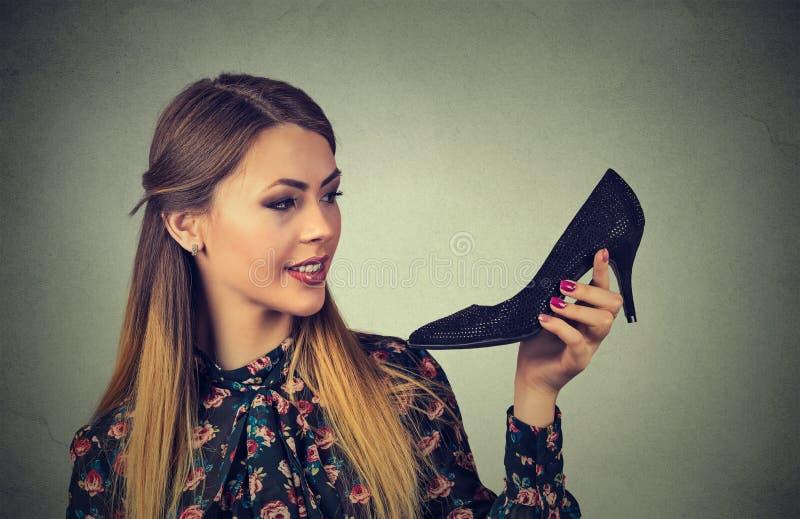 Donna che tiene scarpa nera Il tacco alto di amori delle donne calza il concetto immagine stock libera da diritti