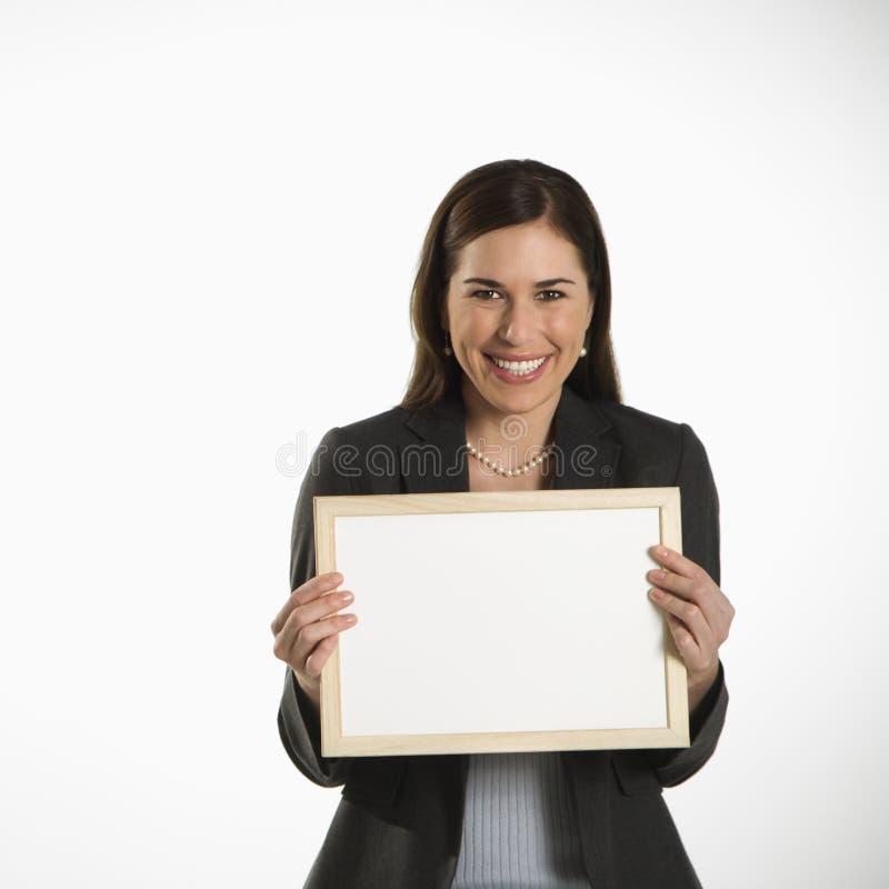 Donna che tiene segno in bianco. fotografia stock