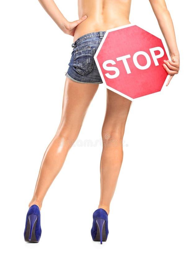 Donna che tiene un arresto del segnale stradale sopra la sua natica fotografia stock