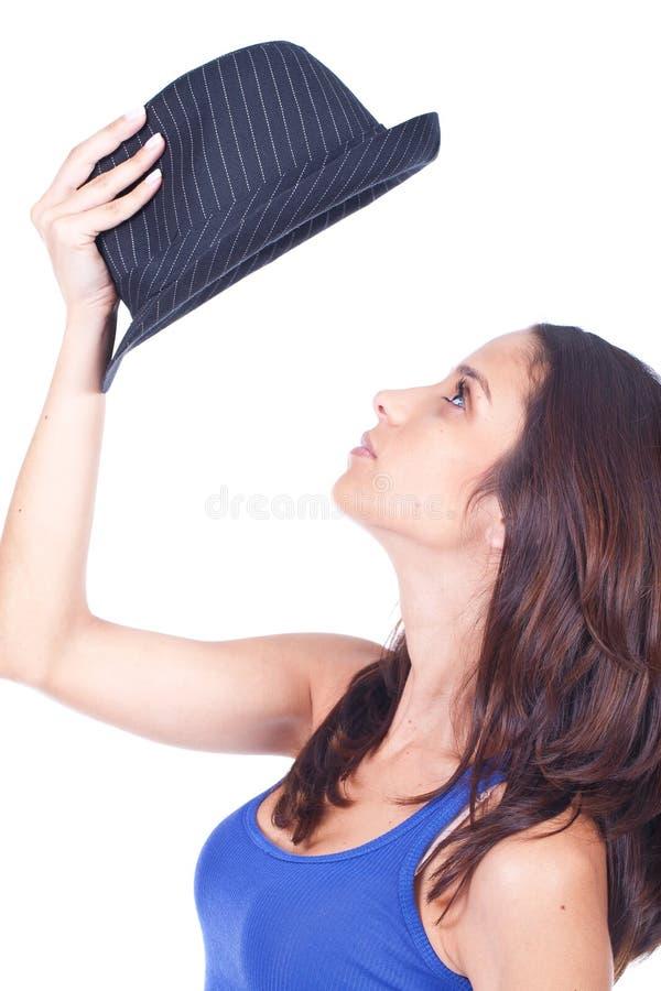 Donna che tiene un cappello nero sopra la sua testa immagini stock libere da diritti