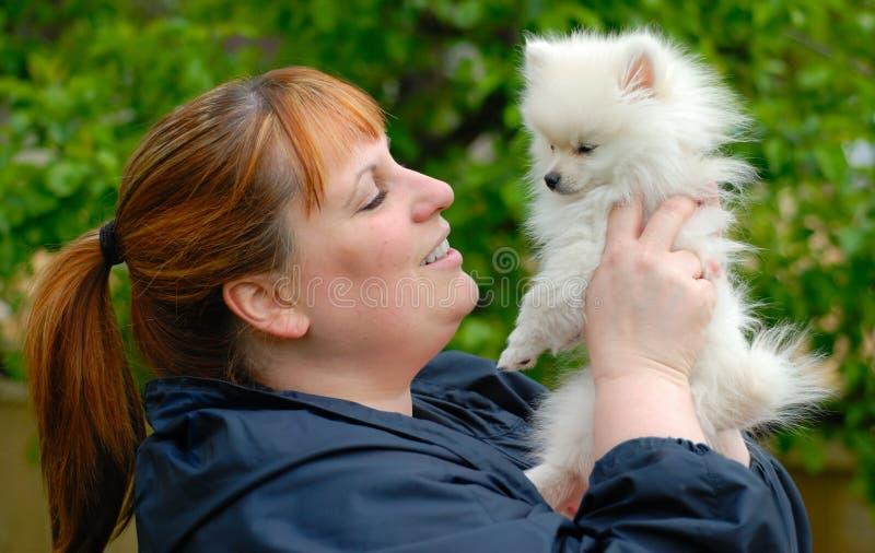 Donna che tiene un cucciolo bianco adorabile di Pomeranian fotografie stock