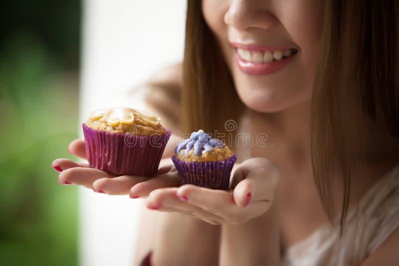 Donna che tiene un dolce della tazza fotografia stock libera da diritti
