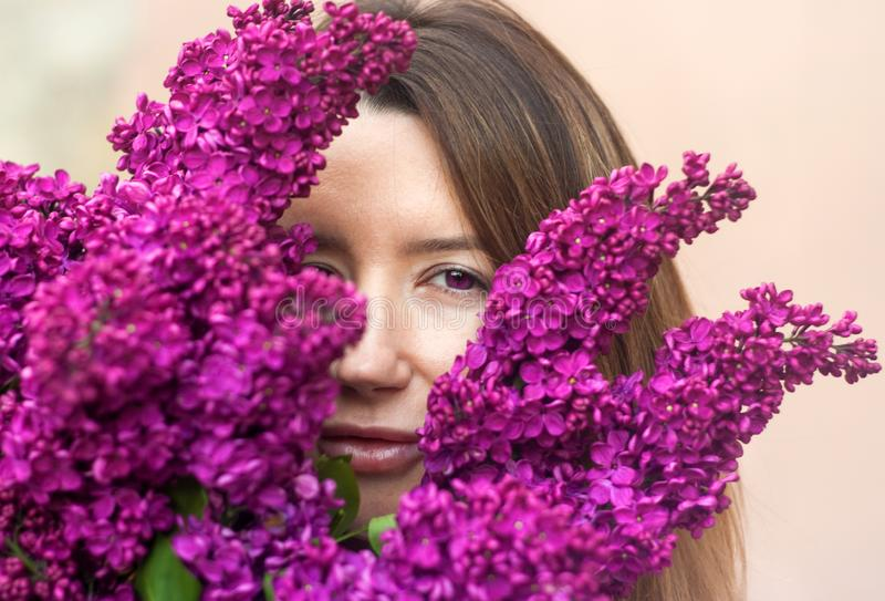 Donna che tiene un grande mazzo dei fiori lilla vicino su immagine stock