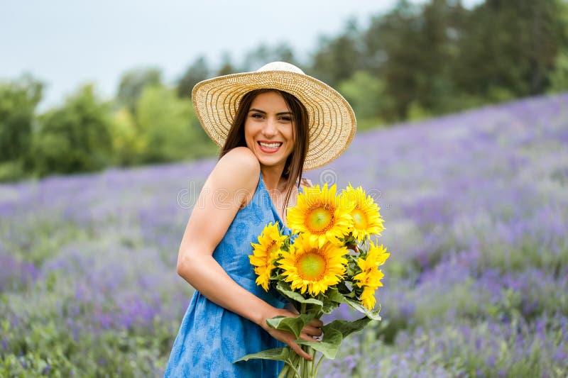 Donna che tiene un mazzo del fiore del sole, ridente fotografia stock libera da diritti