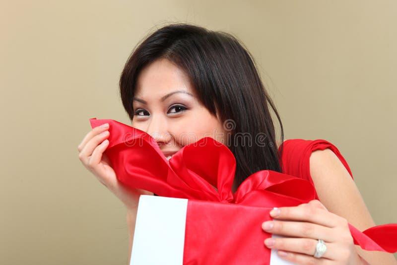 Donna che tiene un pacchetto spostato del regalo fotografia stock libera da diritti