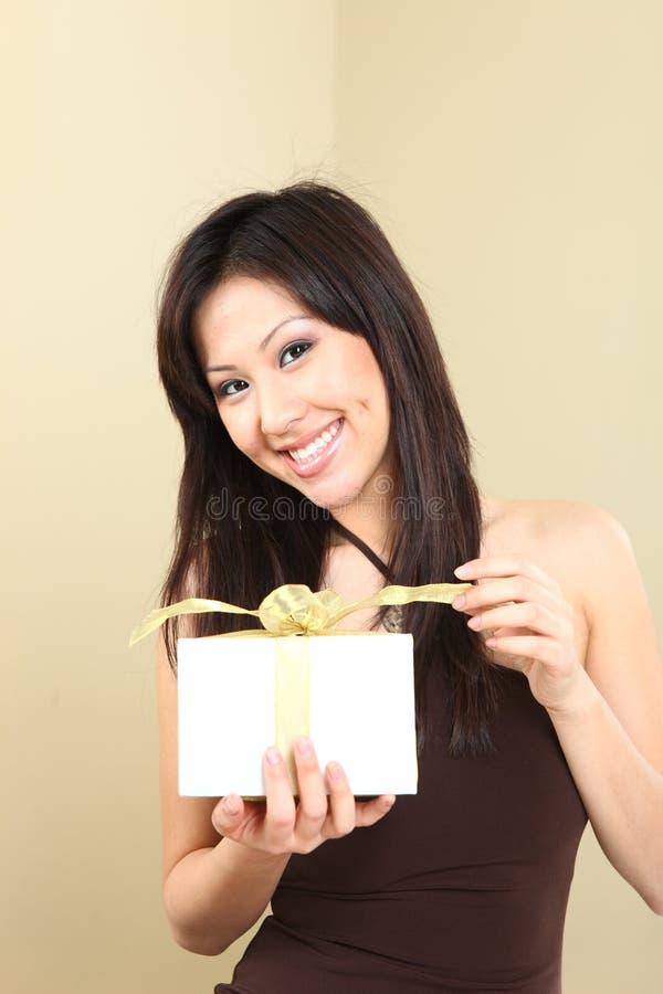Donna che tiene un pacchetto spostato del regalo immagine stock