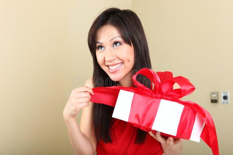 Donna che tiene un pacchetto spostato del regalo fotografie stock